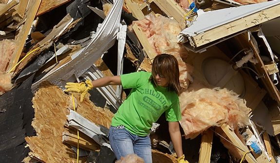 Brooke Hill helps a friend salvage and clean up what they can from her home Thursday, March 1, 2012, in Harrisburg, Ill. A pre-dawn twister flattened entire blocks of homes Wednesday as violent storms ravaged the Midwest and South. (AP Photo/Seth Perlman)