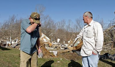 Fred Beaty, left, wipes away tears as his brother Gary Beaty looks at the home near Crossville, Tenn.  where a deadly tornado on Wednesday killed their sister-in-law, Melissa Evans and sent their brother Ricky Beaty to the hospital, Thursday, March 1, 2012. National Weather Service survey teams were set Thursday to evaluate damage from powerful storms that swept across the state, killing three people and damaging dozens of homes.  (AP Photo/Wade Payne)