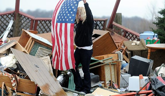 Kendra McKinley pulls a flag from the debris of her grandparents river camp home in Henderson Ky. Wednesday, Feb. 29, 2012. Waves of strong storms ripped roofs off homes, apartment buildings and a bank and destroyed several buildings in north-central Kentucky.  (AP Photo/The Gleaner, Darrin Phegley)
