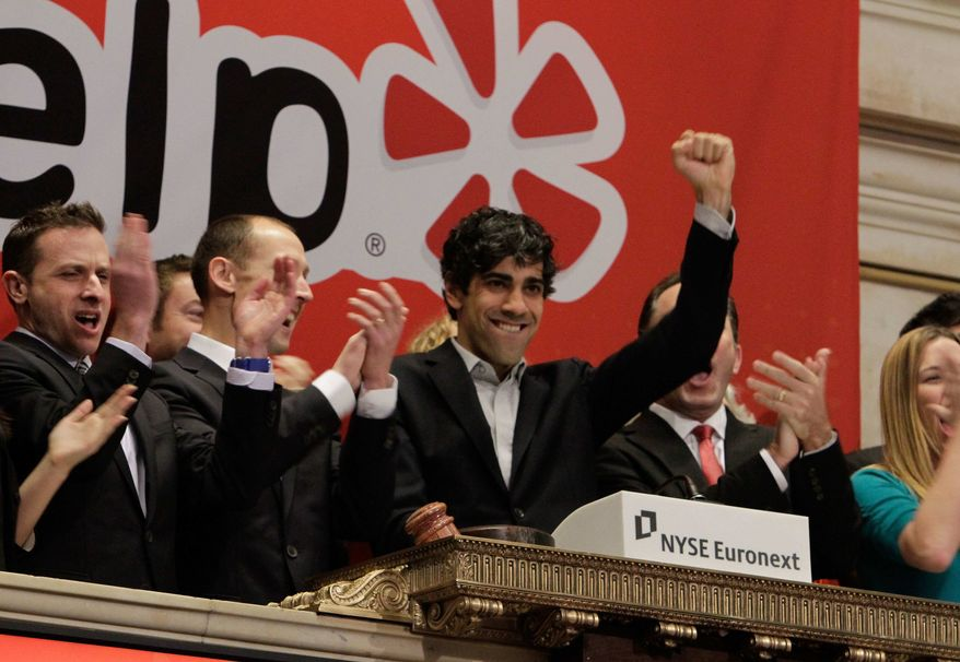 ** FILE ** Jeremy Stoppelman, right center, Yelp co-founder and CEO, salutes during opening bell ceremonies of the New York Stock Exchange Friday, March 2, 2012. Yelp's stock is soaring in its stock market debut Friday. (Associated Press)