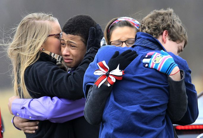 People hug after the burial of Daniel Parmertor at All Soul's Cemetery, Saturday, March 3, 2012, in Chardon, Ohio. Parmertor and two others were fatally shot Monday at Chardon High School. (AP Photo/Tony Dejak)