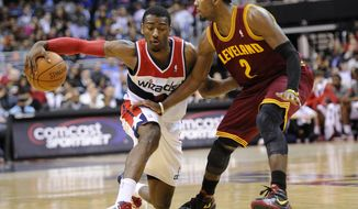 Washington Wizards guard John Wall dribbles against Cleveland Cavaliers guard Kyrie Irving during the second half Saturday, March 3, 2012, in Washington. The Wizards won 101-98. (AP Photo/Nick Wass)