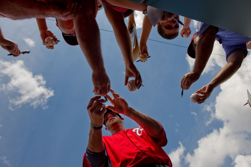 Washington Nationals right fielder Bryce Harper (34) signs autographs for fans before the Washington Nationals play the Houston Astros during spring training at the Osceola County Stadium, Kissimmee, Fla., Saturday, March 3, 2012. (Andrew Harnik/The Washington Times)