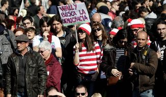 """A young woman holds a banner in Spanish, """"Wally is searching for democracy,"""" at a demonstration against the government's recently approved labor reforms in Madrid. Spain's young people are becoming a """"Lost Generation,"""" with no jobs and seemingly with no real prospects of getting work. (Associated Press)"""
