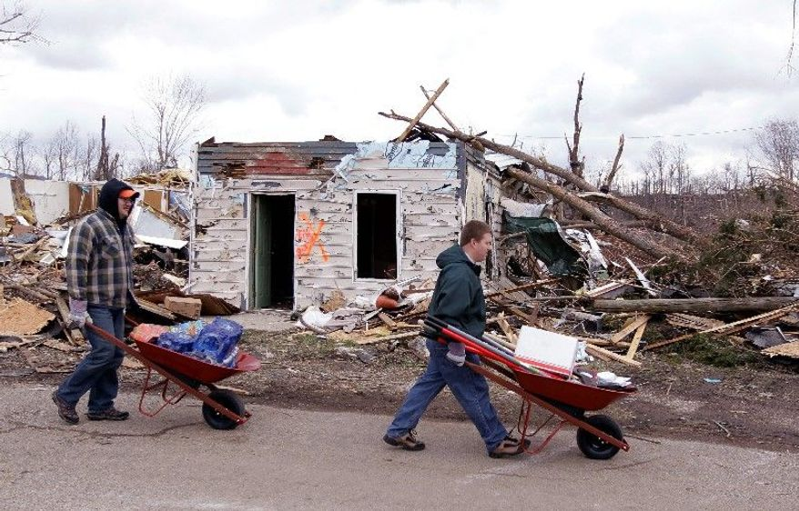 Volunteers look for residents in need of assistance Sunday as they attempt to recover possessions from their homes in Henryville, Ind., destroyed by Friday's tornadoes. With routines and communication disrupted, people have gone back to basics to learn about their loved ones and start rebuilding their lives. At St. Francis Xavier Catholic Church (top), pews during Mass were filled not only with people but also with donated clothing and supplies. (Associated Press)