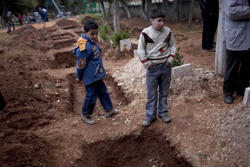 Children attend the funeral of three Free Syrian Army fighters on Saturday, March 3, 2012, in a park converted to a cemetery in Idlib, Syria. (AP Photo/Rodrigo Abd)