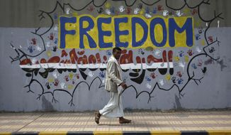 "A Yemeni walks past graffiti that reads, ""Freedom is made by people,"" on a street where protesters demanded a trial for former Yemeni President Ali Abdullah Saleh in Sanaa, Yemen, on Friday, March 2, 2012. (AP Photo/Hani Mohammed)"