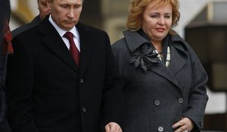 **FILE** Russian Prime Minister Vladimir Putin (left) and his wife, Lyudmila, leave a polling station in Moscow on March 4, 2012. Mr. Putin was running for his previous job of president. (Associated Press)