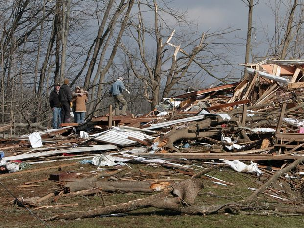 Neighbors comfort one another amid the debris that once was their homes along Highway 160 in Henryville, Ind., on Saturday, March 3, 2012. (AP Photo/Garry Jones)