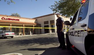 Tempe police Officer T. Williams secures the scene at the Clubhouse Music Venue on Saturday, March 3, 2012, in Tempe, Ariz., after a shooting Friday night outside the club left at least 14 wounded. (AP Photo/The Arizona Republic, David Wallace)