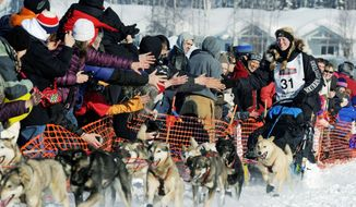 Kristy Berington acknowledges fans Sunday as she makes her way along the trail during the official start of the Iditarod Trail Sled Dog Race in Willow, Alaska. The eight-day trek offers $50,400 and a new truck to the winner. (Anchorage Daily News via Associated Press)