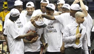 Virginia Commonwealth basketball players congratulate MVP Darius Theus , center, as they celebrate winning the Colonial Athletic Association championship at the Coliseum in Richmond, Va., Monday, March 5, 2012. VCU won the game 59-56. (AP Photo/Steve Helber)