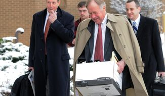 "Richmond attorney William ""Bill"" Broaddus (center), a former Virginia attorney general and attorney for the defendants, carries documents March 5, 2012, into a Christiansburg, Va., courthouse on the first day of a civil trial in the wrongful death case brought against Virginia Tech and the state of Virginia by the parents of two students killed during a campus rampage in 2007. (Associated Press)"
