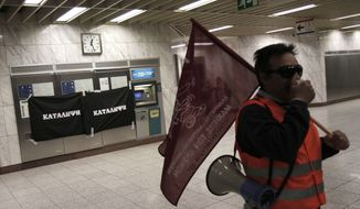 """A protester chants slogans in front of blocked ticket machines with a banner that reads """"Occupation"""" placed on them at the Syntagma Metro station in Athens on Saturday, March 3, 2012, during a protest against the Greek government's austerity measures. (AP Photo/Kostas Tsironis)"""