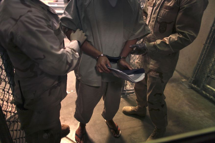 "** FILE ** A handcuffed detainee carries a workbook as he is escorted by guards after attending a ""life skills"" class in the high-security detention facility on Guantanamo Bay Naval Base in Cuba in March 2010. (AP Photo/Brennan Linsley, File)"