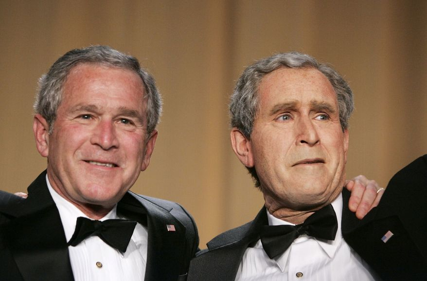 **FILE** President George W. Bush (left) and Steve Bridges, a comedian and President Bush impersonator, gesture April 29, 2006, during the White House Correspondents' Association's 92nd annual awards dinner in Washington. (Associated Press)