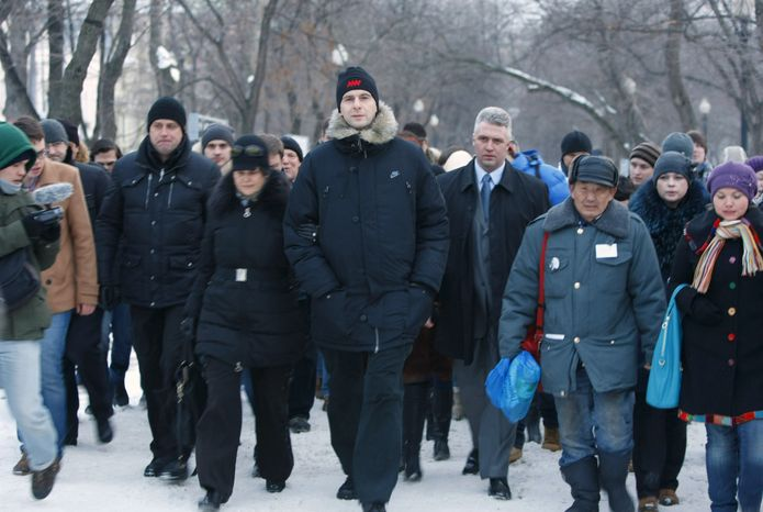 Russian billionaire Mikhail Prokhorov (center), who was a candidate in Sunday's presidential election, heads to a protest rally in downtown Moscow on Monday, March 5, 2012. (AP Photo/Alexander Zemlianichenko)