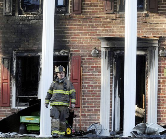 A firefighter exits the front of a heavily damaged two-story home in Hope Mills, N.C., on Tuesday. A Special Forces soldier died trying to rescue his two young daughters during a fire at the house. Edward Cantrell, Isabella Cantrell, 6, and Natalia Cantrell, 4, perished in the blaze. (Associated Press)