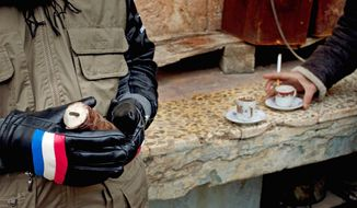 A Free Syrian Army fighter holds a home-made grenade as another fighter has a coffee in Idlib, north Syria, on Tuesday. Syria's president defied mounting international pressure to end the year-old crackdown on an uprising against him. (Associated Press)