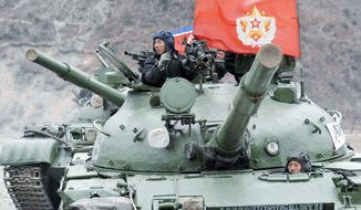 A North Korean soldier operating a tank's gun turret Monday participates in a live-fire drill near country's disputed sea boundary with South Korea. The exercise came amid anger over from Pyongyang over U.S.-South Korean military drills. (Kyodo News via Associated Press)