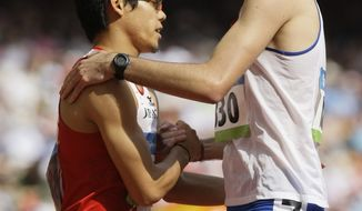 **FILE** Japan's Yuzo Kanemaru (left) and Britain's Martyn Rooney shake hands Aug. 18, 2008, after a heat of the men's 400 meters during the athletics competition in the National Stadium at the Olympics in Beijing. (Associated Press)