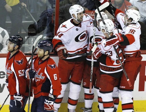 Defeated Washington Capitals players Mike Green (52) and Dennis Wideman (6) pass celebrating Carolina Hurricanes players Jay Harrison (44), Justin Faulk (28), Jeff Skinner (53), and Brandon Sutter (16), after their 4-3 overtime win Tuesday, March 6, 2012, in Washington. (AP Photo/Jacquelyn Martin)