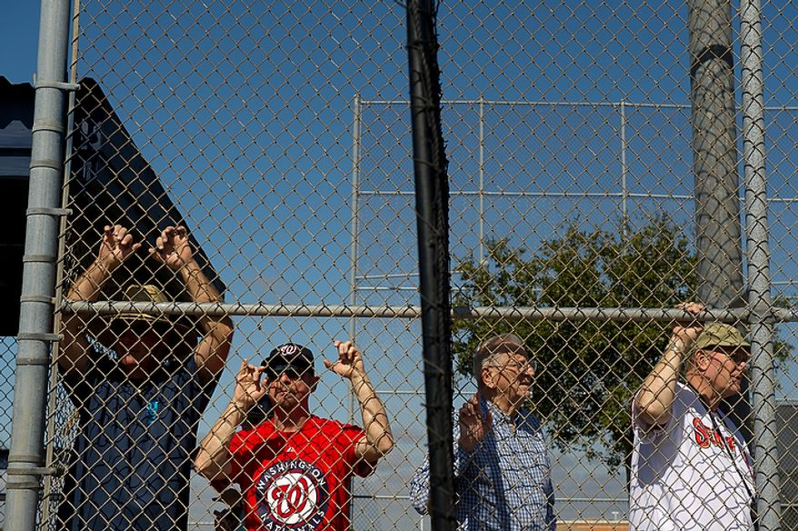 Left to Right: Lenny Strelitz, a player's agent, and fans Steve Heller of Fairfax, Va., Mike DiFrancesco of Viera, Fla., and Dwight Hurst of Harrisburg, Fla., watch the Washington Nationals work out during spring training, Viera, Fla., Tuesday, February 28, 2012. (Andrew Harnik/The Washington Times)