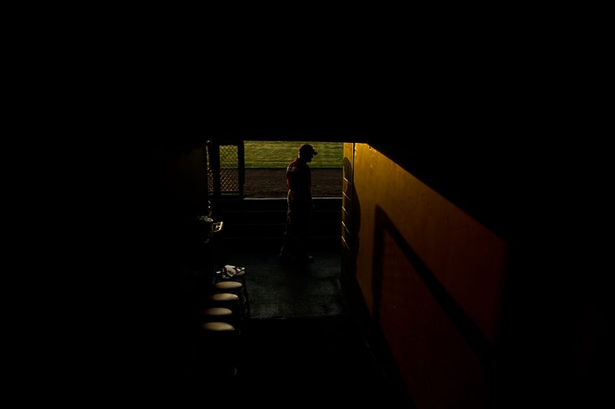 A security guard walks through the dugout in the early morning hours before the Washington Nationals practice during spring training at Space Coast Stadium, Viera, Fla., Wednesday, Feb. 29, 2012. (Andrew Harnik/The Washington Times)
