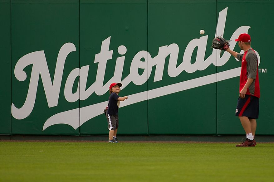 Washington Nationals relief pitcher Sean Burnett (17) throws with his 3 year old son, Sebastian, in the outfield during spring training at Space Coast Stadium, Viera, Fla., Thursday, March 1, 2012. (Andrew Harnik/The Washington Times)