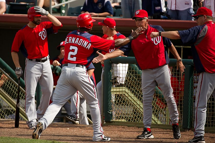 Washington Nationals center fielder Roger Bernadina (2) is congratulated for scoring by Washington Nationals manager Davey Johnson (5), second from right, and others as the Washington Nationals play the Houston Astros during spring training at the Osceola County Stadium, Kissimmee, Fla., Saturday, March 3, 2012. (Andrew Harnik/The Washington Times)