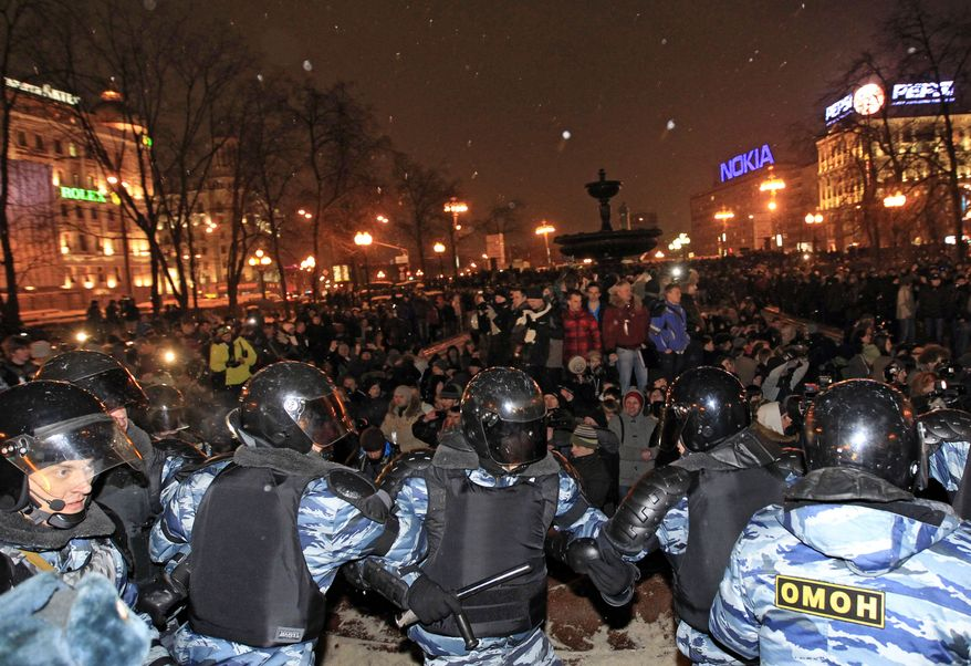 Police officers block opposition demonstrators after a massive rally in Pushkin Square in downtown Moscow on Monday, March 5, 2012, to protest Sunday's presidential election. (AP Photo/Sergey Ponomarev)