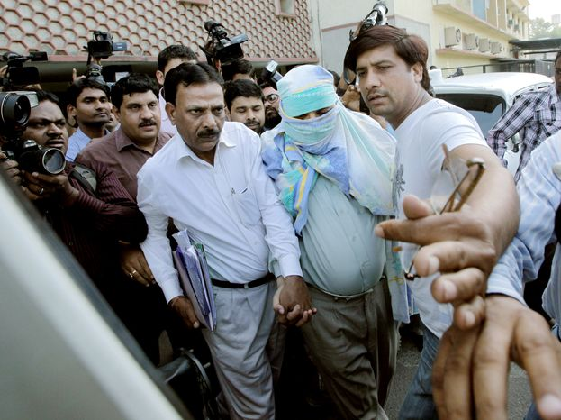 Policemen escort Syed Mohammed Kazmi, linked to last month's bombing of an Israeli diplomat's vehicle, from a local court in New Delhi on Wednesday. The arrest of the Indian journalist is the first apparent breakthrough in an attack that Israel accused Iran of orchestrating. (Associated Press)