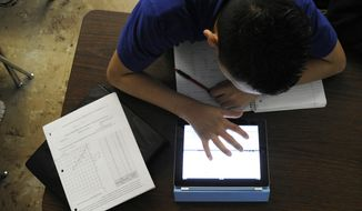 **FILE** Grant Beacon Middle School student Jeriah Garcia, 13, works out an algebra problem on his school-supplied iPad in class at Grant, Colo. (Associated Press/The Denver Post)