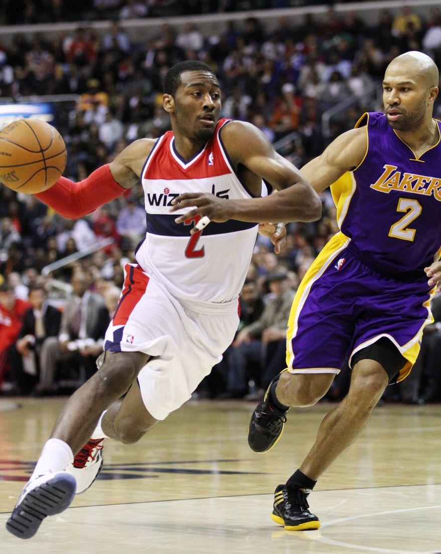 Washington Wizards guard John Wall drives to the basket against Los Angeles Lakers point guard Derek Fisher in the fourth quarter at Verizon Center in Washington, Wednesday, March 7, 2012. The Wizards won 106-101. (AP Photo/Jacquelyn Martin)