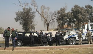 Iraqi security forces inspect the scene of a car bomb attack in the Mansour neighborhood of Baghdad on Wednesday, March 7, 2012. (AP Photo/Khalid Mohammed)