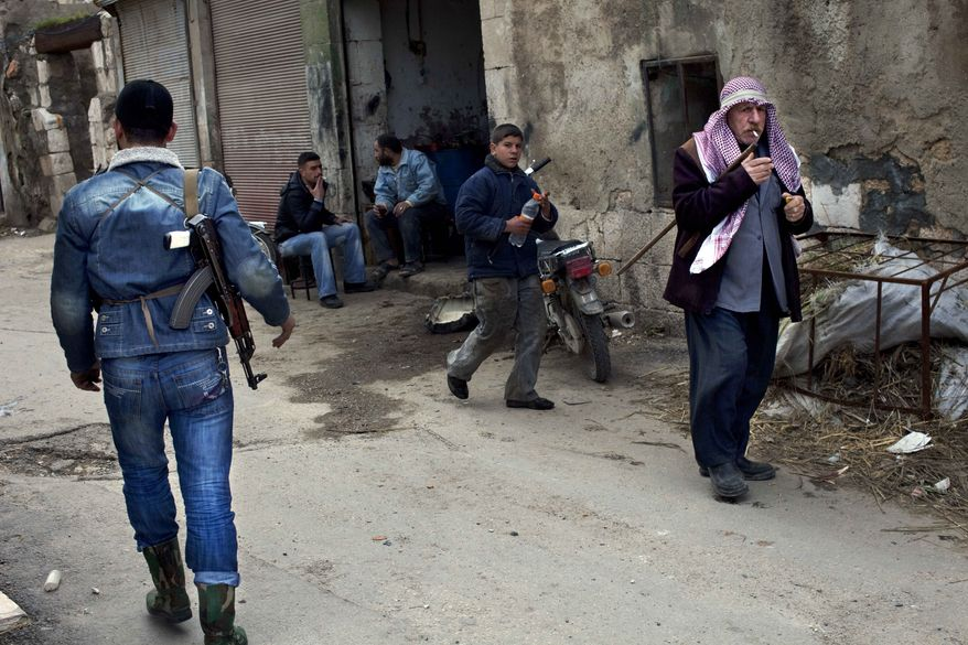 Syrians walk past a Free Syrian Army fighter (left) in the old city of Idlib, Syria, on Monday, March 5, 2012. (AP Photo/Rodrigo Abd)