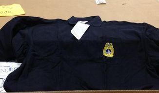 A photograph obtained by The Washington Times shows one of 1,750 brand-new, National Fire Protection Association-compliant polo-style shirts that have sat unused in crates in the D.C. fire department's warehouse because they display an outdated patch. The shirts cost about $70,000.