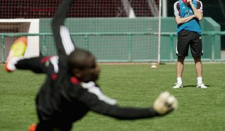 D.C. United coach Ben Olsen watches goalkeeper Bill Hamid dive for a ball during practice at RFK Stadium. United's season kicks off Saturday night at home against Sporting Kansas City. (Andrew Harnik/The Washington Times)