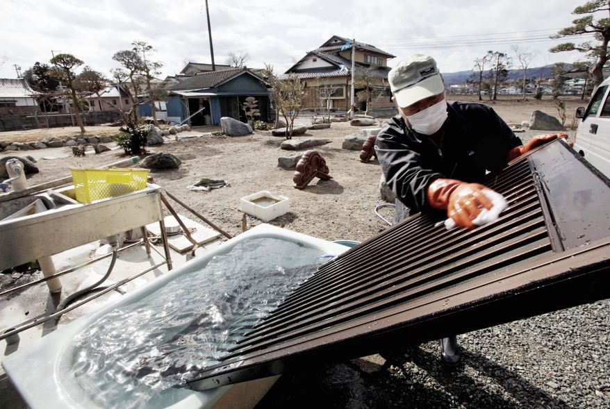 A man washes a door in a bathtub outside a home in Hirono, Japan, part of an attempt to remove radioactive contamination. Hirono is outside the nuclear exclusion zone around the Fukushima Dai-ichi nuclear plant. Officials say there is no successful example they can follow for the cleanup, and they don't know how to judge the effectiveness of a process that is expected to last for years or even decades. (Associated Press)
