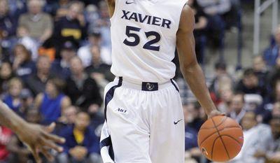 Xavier guard Tu Holloway in action against Rhode Island in an NCAA college basketball game, Wednesday, Feb. 8, 2012, in Cincinnati. (AP Photo/Al Behrman)