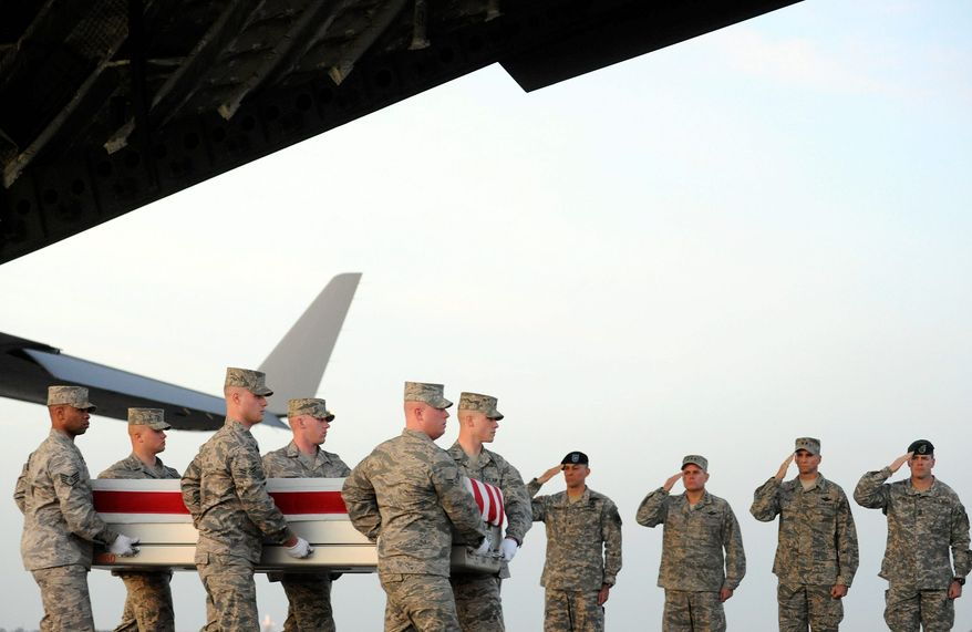 An Air Force carry team moves a transfer case containing the remains of Lt. Col. John D. Loftis on Monday, Feb. 27, 2012, at Dover Air Force Base, Del. According to the Department of Defense, Col Loftis, 44, of Paducah, Ky., died Feb. 25 from wounds suffered during an attack at the Afghan Interior Ministry in Kabul. (Associated Press)