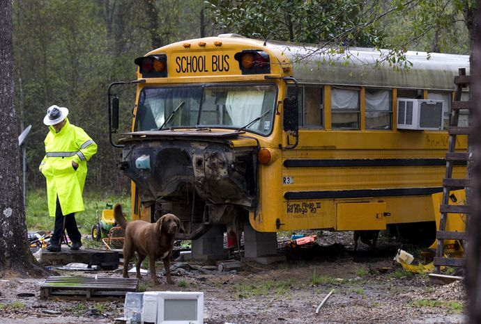 A Montgomery County sheriff's deputy walks away March 7, 2012, from an old school bus in Spendora, Texas, where an 11-year-old girl and her five-year-old brother were found living on their own. Both of the children's parents are in prison, officials said. (Associated Press/Houston Chronicle)