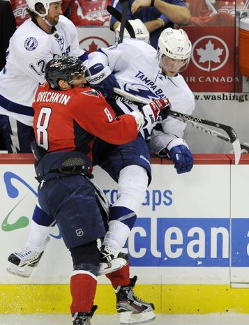 Washington Capitals left wing Alex Ovechkin checks Tampa Bay Lightning defenseman Victor Hedman into the bench during the third period Thursday, March 8, 2012, in Washington. The Capitals won 3-2 in overtime. (AP Photo/Nick Wass)