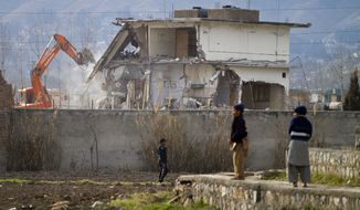 A police commando stands guard on Sunday, Feb. 26, 2012, as authorities use heavy machinery to demolish Osama bin Laden's compound in Abbottabad, Pakistan. (AP Photo/Anjum Naveed)