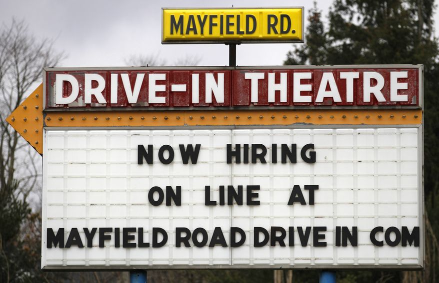 A help-wanted sign displays outside the Mayfield Drive-In movie theater in Chardon, Ohio, on March 8, 2012. (Associated Press)