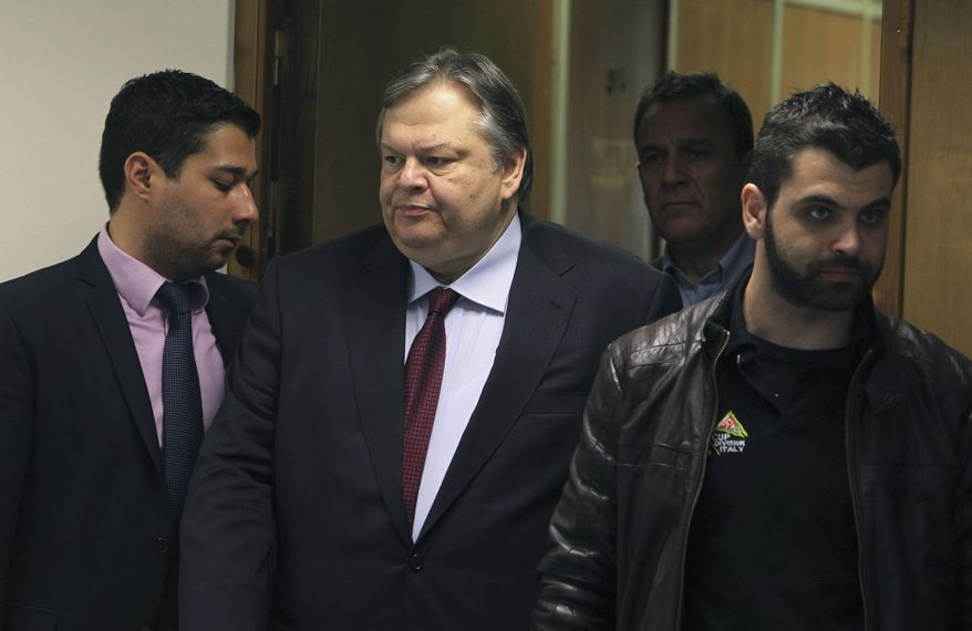 Greece's Finance Minister Evangelos Venizelos (center), surrounded by his personal security, arrives March 9, 2012, for a news conference in Athens. (Associated Press)