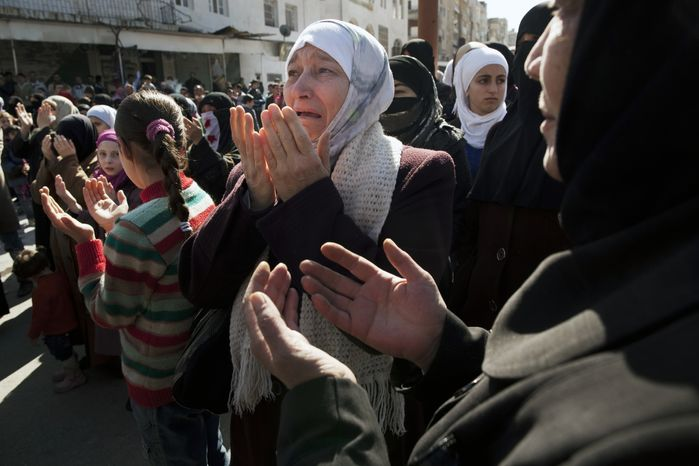 A woman weeps as she prays during an anti-government demonstration in Idlib, Syria, on March 9, 2012. (Associated Press)
