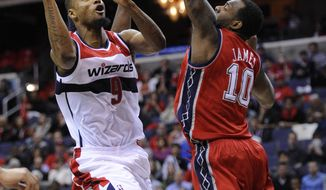 **FILE** Washington Wizards forward Rashard Lewis (9) goes to the basket against New Jersey Nets forward Damion James (10) during the Nets' 90-84 win in Washington on Dec. 26, 2011. (Associated Press)