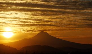 ** FILE ** The sun rises March 8, 2012, over Mount Hood in Portland, Ore. The largest solar storm in five years has engulfed Earth, but scientists say the planet has lucked out so far. (Associated Press)