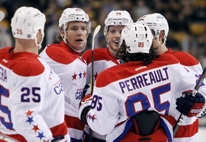 Washington Capitals' Alexander Semin (28) celebrates his goal with teammates Jason Chimera (25), John Carlson (74), Karl Alzner (27) and Mathieu Perreault (85) in the first period of an NHL hockey game against the Boston Bruins in Boston, Saturday, March 10, 2012. (AP Photo/Michael Dwyer)